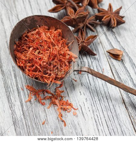 saffron in spoon with anise on wooden background