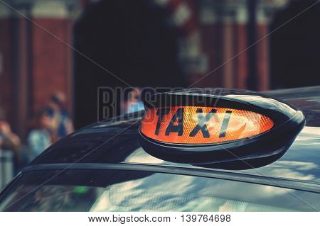 The sign and light on the roof of a typical black cab taxi in London, England.
