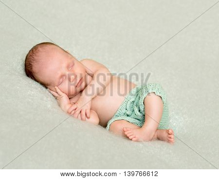 sleeping baby in pants with hand under his head and crossed legs on blanket