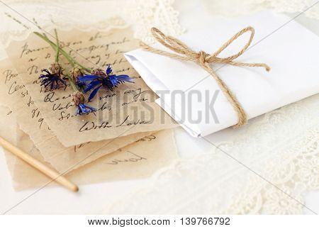Romantic love letters (text unrecognizable) on parchment thin paper, blue dried meadow flowers, handcrafted paper gift wrapping . Light lace background.