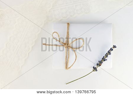 Soft romantic background. White paper envelope gift with twine bow, dried lavender flower, blur lace. Light delicate mockup.
