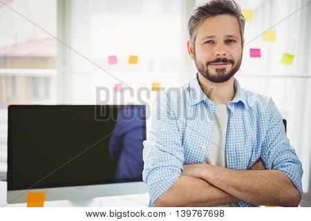 Portrait of young businessman sitting at desk in creative office