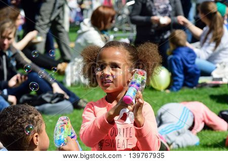 LONDON ENGLAND 9 May 2015: Small girl with bubbles