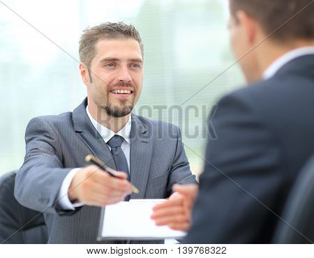 Portrait man in formalwear stretching out clipboard with paper and pointing it with pen while