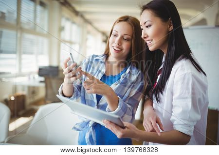 Female colleagues discussing with digital tablet and mobile phone in creative office