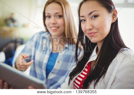 Portrait of female colleagues with digital tablet in creative office