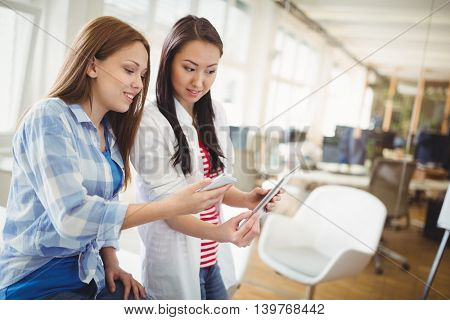 Female colleagues holding digital tablet and mobile phone in creative office