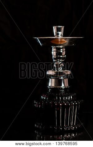 Deep red glass tobacco smoking hookah taken into pieces on the dark background.