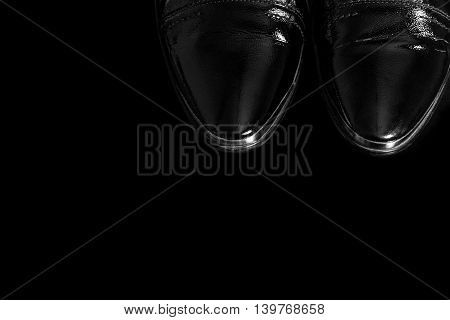 Fragmentary image of patent-leather male shoes on the luxury black background