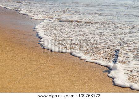 Soft ocean wave on the sandy beach selective focus