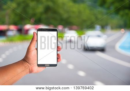 hand of man hold mobile phone over blurred car on the road