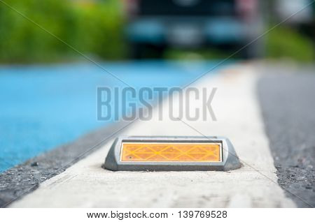 The Soft Focus Of Reflector Or Stud On Asphalt Road