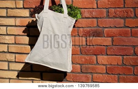 Linen Bag with Fresh Lettuce Salad against the background of a brick wall closeup