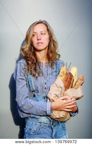 Stylish Blonde Woman Is Holding In Their Hands A Paper Bag With Baguettes