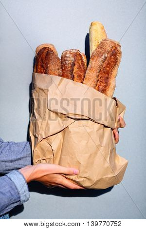 French Baguette. Paper Bag With Baguettes In Hands Of Woman Closeup