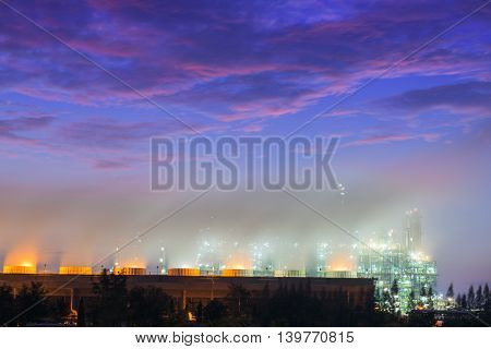 Steaming cooling tower of oil refinery plant Twilight shot.