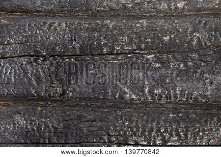 Charred black wooden wall. Abstract background with a burned boards textures closeup