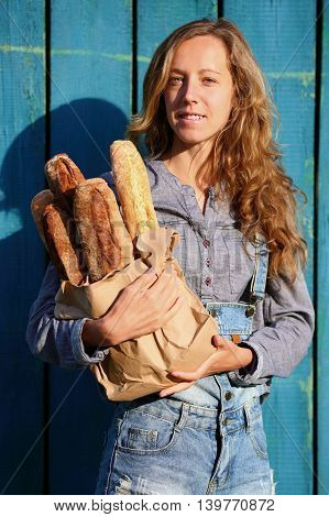 Blonde Woman Is Holding In Their Hands A Paper Bag With Fresh Baguettes