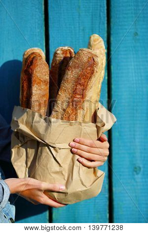 Baguettes. Paper Bag With Baguette In Hands Of Woman Closeup