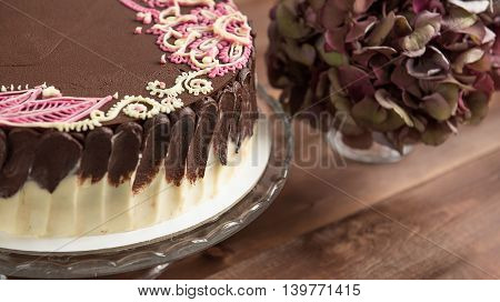 Sponge cake with mehendi patterns on a glass stand. Close-up.