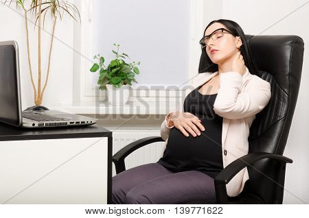 Tired pregnant woman sitting at workplace in the office