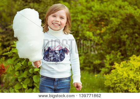 girl smiling and holding cotton candy in the summer