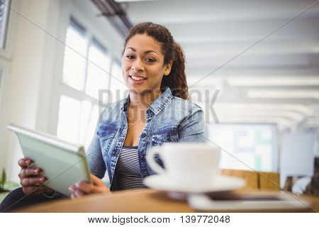Portait of happy businesswoman holding digital tablet in creative office