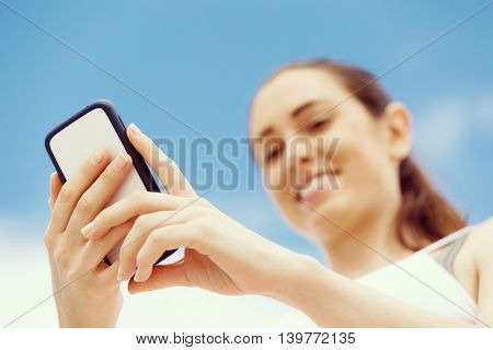 Female runner with her mobile smart phone standing outdoors