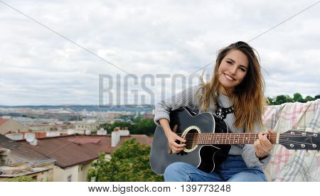 Girl playing the guitar on the background of the park on the roof