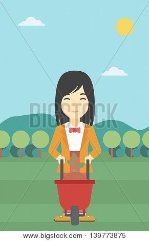 An asian young woman standing with a plant and soil in a wheelbarrow on the background of mountain landscape. Vector flat design illustration. Vertical layout.