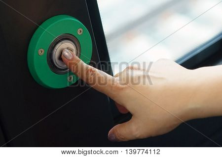 A woman presses the index finger to the green exit button.