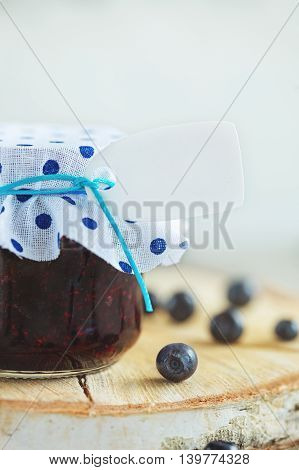 Fresh blueberry homemade jam in jar with tag and berry on  wood background. healthy organic and vegan food.Toning image