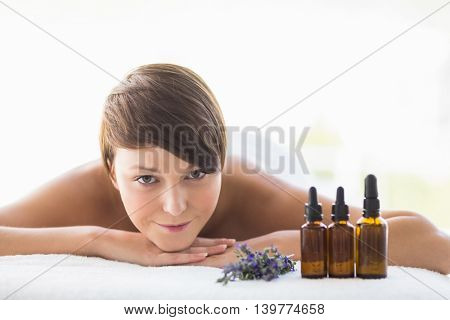 Portrait of young woman relaxing on massage table at spa