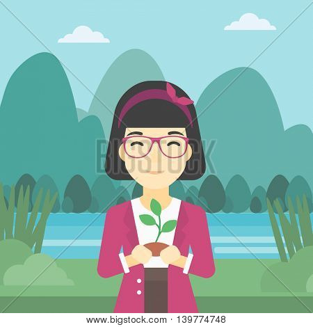 An asian young woman holding in hands a small plant in soil on the background of landscape with mountains and river. Vector flat design illustration. Square layout.