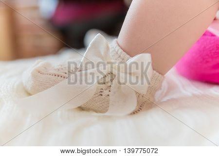Close-up photo of newborn baby foot in beautiful sock