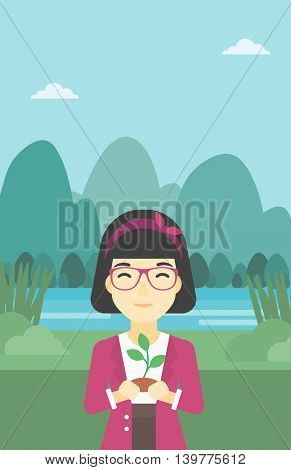 An asian young woman holding in hands a small plant in soil on the background of landscape with mountains and river. Vector flat design illustration. Vertical layout.