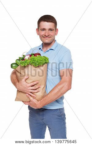 Smiling young man holding shopping bag full of groceries isolated at white background. Healthy food shopping. Paper package with vegetables and fruits, happy male buyer came from market