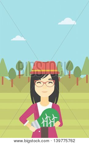 An asian woman standing on the background of green forest and holding in hands a big light bulb with small wind turbines inside. Green energy concept. Vector flat design illustration. Vertical layout.