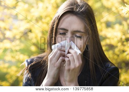 Teenager girl with pollen allergy over flowers