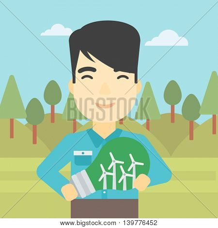 An asian man standing on the background of green forest and holding in hands a big light bulb with small wind turbines inside. Green energy concept. Vector flat design illustration. Square layout.