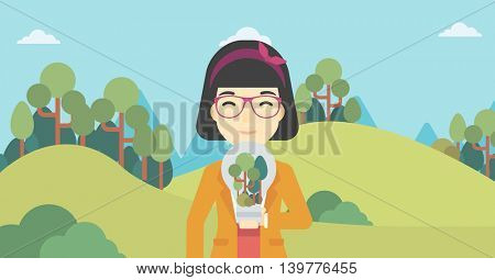 An asian woman standing on the background of green forest and holding in hands a big lightbulb with trees inside. Green energy concept. Vector flat design illustration. Horizontal layout.