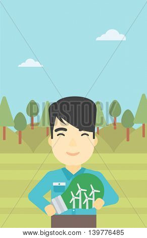 An asian man standing on the background of green forest and holding in hands a big light bulb with small wind turbines inside. Green energy concept. Vector flat design illustration. Vertical layout.