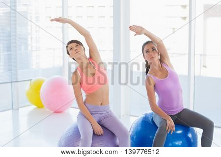 Women sitting on exercise ball at health club