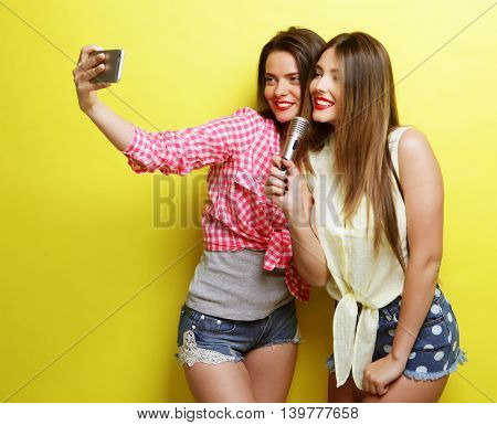 two beauty hipster girls with a microphone  take selfi
