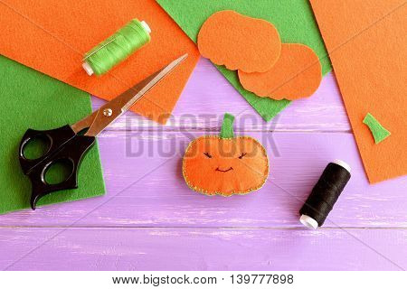 Easy sew stuffed fabric pumpkin decoration, threads, scissors, needle, felt sheets and patterns on lilac wooden table. Halloween pumpkin idea made with felt. Kids Halloween background