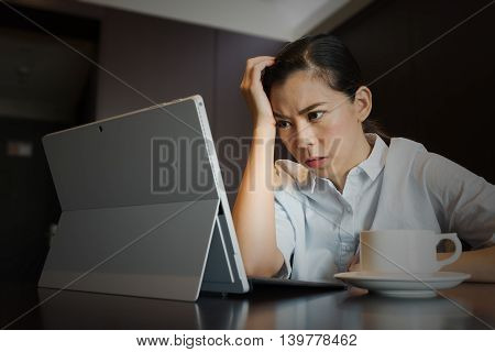 Frustrated businesswoman having headache hold hand head upset while working, sitting using taplet Laptop Computer, work failure stress and problems Concept.