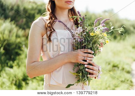 Pregnant Woman Holding Wildflowers At The Park