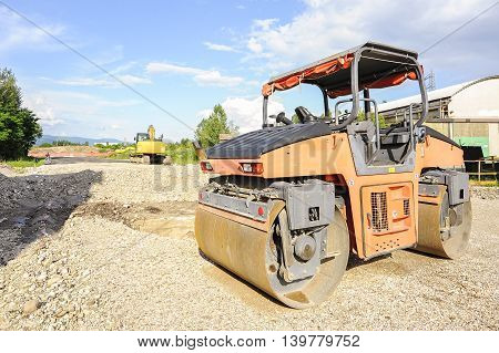 Road roller working at road construction site.