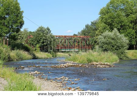 river with nice green vegetations on its banks and railway bridge across it