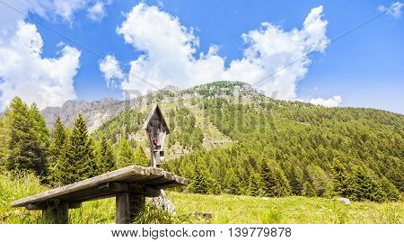 Mountain panorama with table and benches for resting and crucified. Julian Alps Friuli Italy
